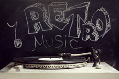 Popular retro music. Retro old turntable with a plate on the background of the inscription in chalk on a blackboard Stock Photos