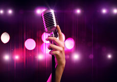 Popular singer. Close up of female hand on blurred background holding microphone Stock Photo