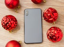 A popular smartphone with Christmas balls. The smartphone rests on a wooden surface on the screen next to the Christmas balls Stock Photography
