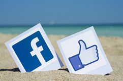 Popular social media icons. Facebook like logos for e-business, web sites, mobile applications, banners, printed on paper and placed in the sand against the sea Stock Photos