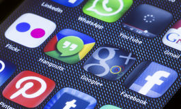 Popular social media icons hangouts google plus and other on smart phone screen close up Stock Images