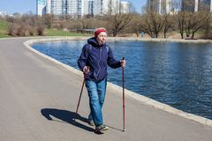 Popular sport around the world-Nordic walking. an elderly woman goes to the spring Park . Active people on the street. Stock Photos