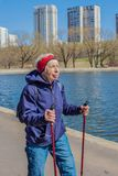 Popular sport around the world-Nordic walking. an elderly woman goes to the spring Park . Active people on the street. Stock Photo