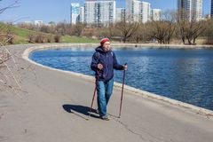 Popular sport around the world-Nordic walking. an elderly woman goes to the spring Park . Active people on the street. Royalty Free Stock Photography