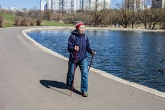 Popular sport around the world-Nordic walking. an elderly woman goes to the spring Park . Active people on the street. Royalty Free Stock Images