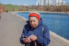 Popular sport around the world-Nordic walking. an elderly woman goes to the spring Park . senior uses her phone while walking. Stock Photography