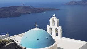The popular three bells and blue dome in fira on the island of santorini