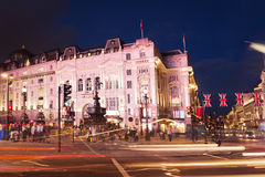 Popular tourist Picadilly circus with flags union jack in night Stock Image