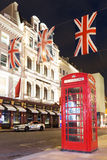 Popular tourist Red phone booth with flags union jack in night l Stock Photo