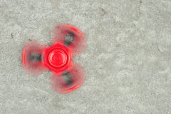Popular Tri Fidget Hand Spinner spinning on stone background. Stock Photography