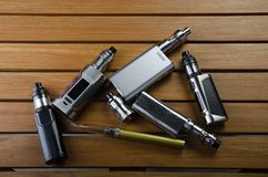 Electronic cigarette mods for ecig over a wooden background. vape devices and cigarette. Popular vaping e cig device mod.electronic cigarette over a wood royalty free stock images