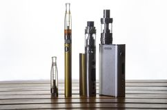 Electronic cigarette mods for ecig over a wooden background. vape devices and cigarette. Popular vaping e cig device mod.electronic cigarette over a wood stock images