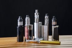 Electronic cigarette mods for ecig over a wooden background. vape devices and cigarette. Popular vaping e cig device mod.electronic cigarette over a wood stock image