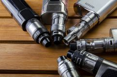 Electronic cigarette mods for ecig over a wooden background. vape devices and cigarette. Popular vaping e cig devices mod.electronic cigarette over a wood royalty free stock photo