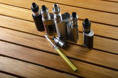 Electronic cigarette mods for ecig over a wooden background. vape devices and cigarette. Popular vaping e cig devices mod.electronic cigarette over a wood stock images