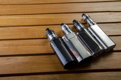 Electronic cigarette mods for ecig over a wooden background. vape devices and cigarette. Popular vaping e cig devices mod.electronic cigarette over a wood royalty free stock photos