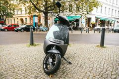 A popular vehicle in the city is called an electric scooter. In the background a street in Berlin. Stock Images