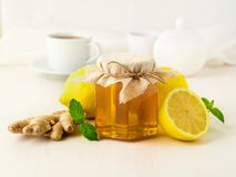 Popular Ways To Treat A Cold - A Jar Of Honey, Ginger, Mint, Lemons On White Background, Side View Stock Photography
