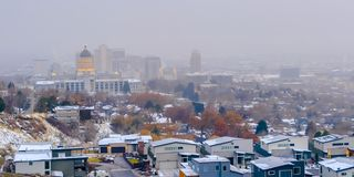 The populous Salt Lake City downtown with a hazy sky background in winter. The historic Utah Stae Capital Building towers majestically over the cityscape stock image