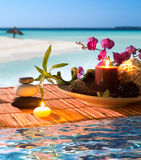 Popurrí, bowl, candles, cinnamon, on tropical water. Preparation for spa: candle, massage with zen black stones, purple orchid and bamboo stalk Stock Photo