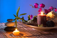 Popurrí, bowl, dried flowers, candles , cinnamon. Preparation for spa: candle, massage with zen black stones, purple orchid and bamboo stalk Stock Photo