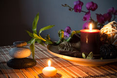 Popurrí, bowl, dried flowers, candles , dark. Preparation for spa: candle, massage with zen black stones, purple orchid and bamboo stalk Stock Image