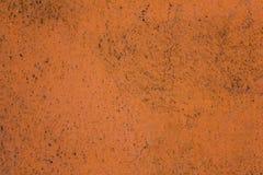 Porös grynig vägg för gammal smutsig yttersida för terrakotta orange med svarta prickar och en stor spricka ungefärlig textur royaltyfria foton