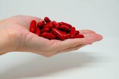 Por completo de cápsulas rojas en una mano Imagen de archivo