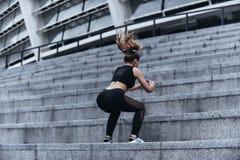 Por completo de la energía Mujer joven moderna en la ropa del deporte que salta mientras que ejercita en las escaleras al aire li Foto de archivo libre de regalías