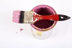 Por completo de la lata y de la brocha rosadas de la pintura fotografía de archivo
