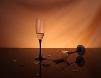 Por completo del vino y de las copas quebradas sobre fondo anaranjado Fotos de archivo libres de regalías