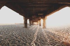 Por debajo el puente de madera en la playa arenosa imagen de archivo