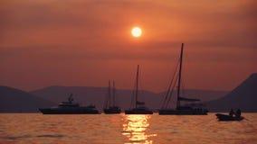 Por do sol ótimo sobre o litoral, céu surpreendente Iate que navegam, um homem em um barco que enfileira à costa com uma menina p video estoque