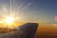 Por do sol acima da asa de um avião com céu romântico Imagens de Stock Royalty Free
