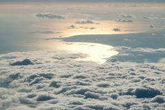 Por do sol acima das nuvens da janela do avião Fotos de Stock