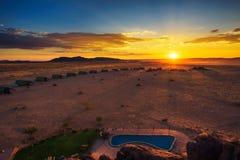Por do sol acima dos chalés pequenos de um alojamento do deserto perto de Sossusvlei em Namíbia foto de stock