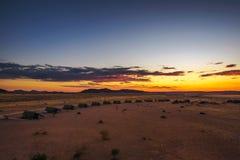 Por do sol acima dos chalés pequenos de um alojamento do deserto perto de Sossusvlei em Namíbia imagem de stock