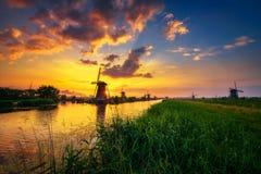 Por do sol acima dos moinhos de vento holandeses velhos em Kinderdijk, Países Baixos Foto de Stock