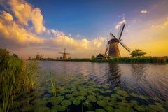 Por do sol acima dos moinhos de vento holandeses velhos em Kinderdijk, Países Baixos Fotos de Stock Royalty Free