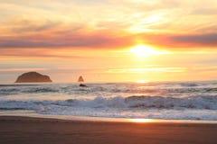Por do sol adiantado luminoso brilhante sobre afloramento rochosos na costa de Oregon Fotos de Stock Royalty Free
