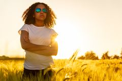 Por do sol adolescente dos óculos de sol da menina afro-americano da raça misturada no campo imagens de stock