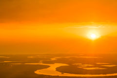 Por do sol alaranjado bonito sobre o rio, capturado dos aviões Imagens de Stock
