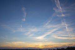 Por do sol alaranjado dourado e céu azul profundo com contraste plúmeo branco das nuvens imagens de stock