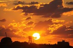 Por do sol alaranjado e amarelado sobre a torre de água Foto de Stock Royalty Free