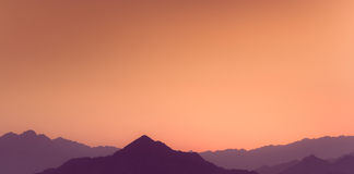 Por do sol alaranjado e amarelo acima das camadas de montanhas Fotografia de Stock