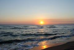 Por do sol alaranjado nas ondas do mar, conceito para a paz e abrandamento Imagens de Stock