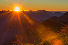 Por do sol alaranjado vermelho com raios de sol à grama Fotos de Stock Royalty Free
