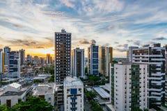 Por do sol amarelo bonito com construções da skyline na praia de Viagem da boa, Recife, Pernambuco, Brasil fotos de stock royalty free