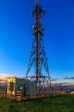 Por do sol atrás da torre das telecomunicações Fotos de Stock