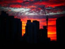 Por do sol atrás das construções com o céu nebuloso bonito fotografia de stock